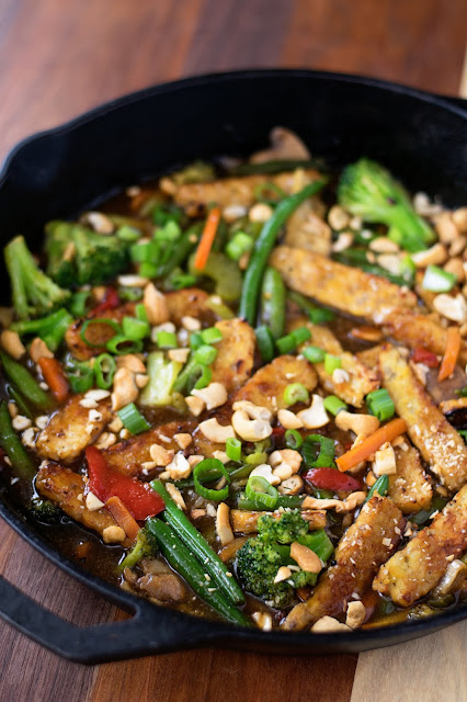 The finished pan of Vegan Tempeh Stir Fry topped with sliced green onion and chopped cashews.