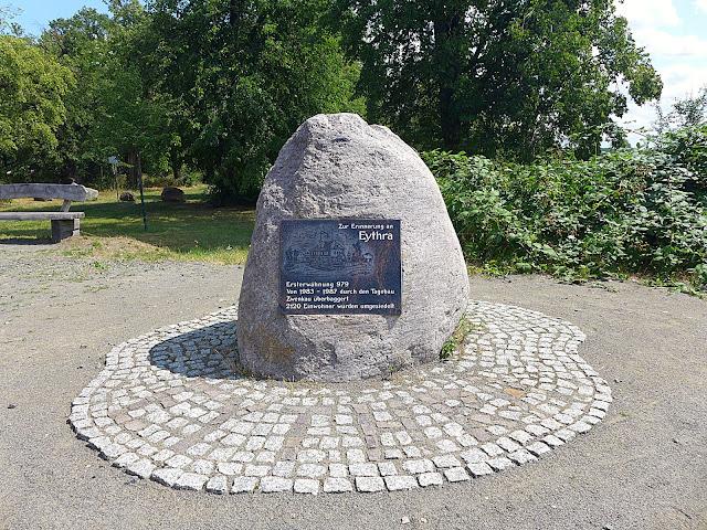 Gedenkstein im Vordergrund, dahinter Sitzbank und Teil der historischen Lindenallee