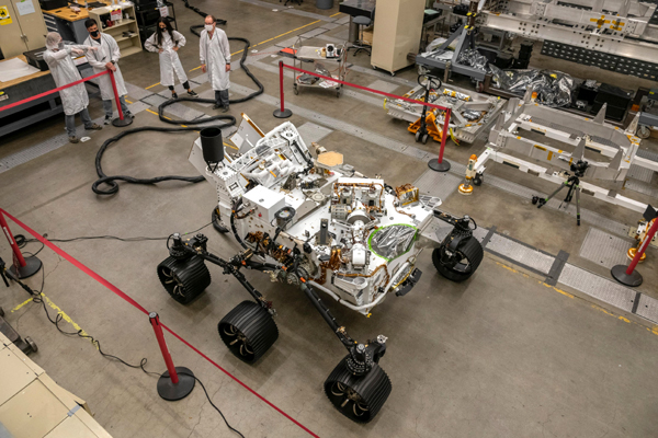 Engineers test-drive the OPTIMISM rover inside a warehouse-like assembly room at NASA's Jet Propulsion Laboratory near Pasadena, California.