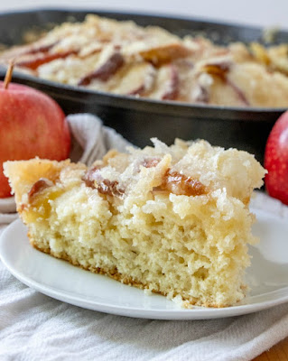 Looking across a slice of dutch apple cake, showing the cake layer with apples on top, remaining cake in background