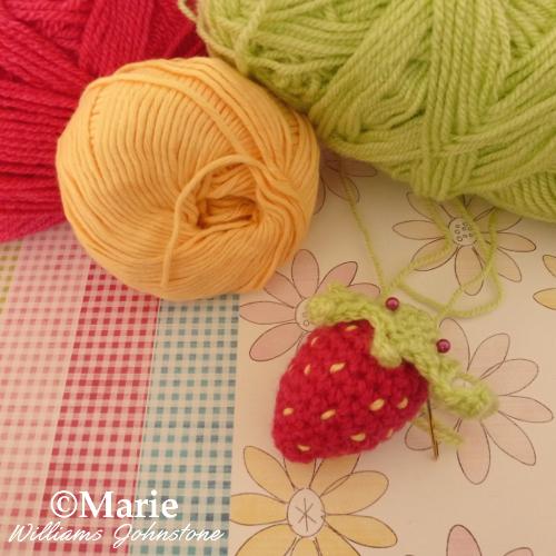 Pinning the green strawberry stalk to the crochet plush strawberry