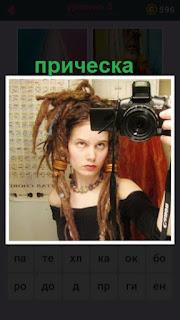 девушка сделала прическу и фотографирует сама себя фотоаппаратом