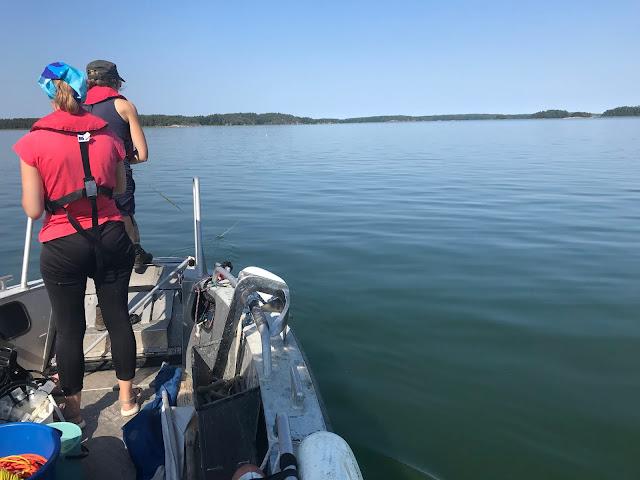 Vene tyynellä merellä, kaksi henkilöä laittamassa mittanauhaa veteen