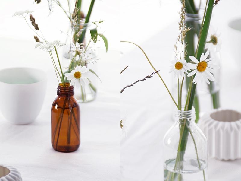 Sommerliche Tischdeko mit Wiesenblumen und Gräsern in Glasflaschen, Teelichtern und weißer Tischdecke | Tasteboykott