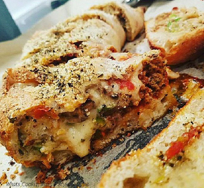 this is a stuffed pizza roll called stromboli and an italian stuffed pizza rolled with sausage, peppers and lots of melted cheeses inside of it