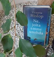 Kirja kukkaruukussa, nojaa ison viherkasvin runkoon, alla vaaleita koristekiviä, vasemmassa reunassa kasvin oksa lehtineen