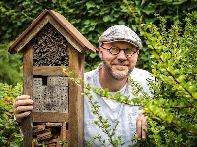 Marcin Zych w ogrodzie z hotelikiem dla zapylaczy