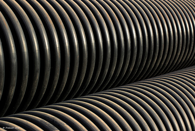 A Minimalist Picture of the Curves of a plastic Industrial Pipes forming a Repetitive Pattern, Shot via Canon 100mm Prime Macro L Series Lens mounted on Canon 600D Camera.