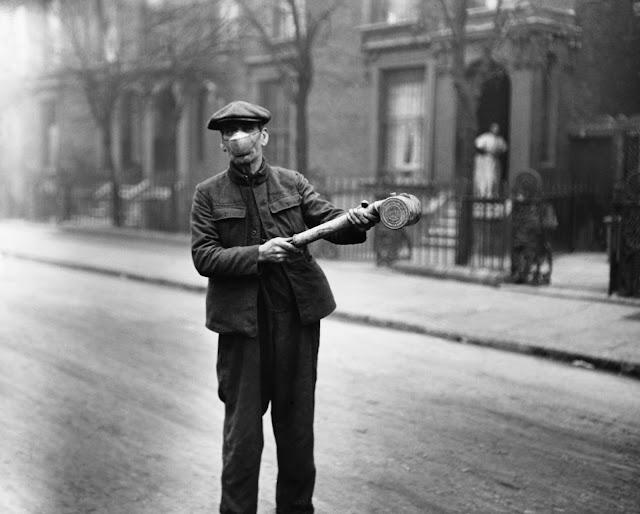 """Bir maske takan bir adam, 1920 dolaylarında Birleşik Krallık'ta bilinmeyen bir """"anti-grip"""" maddesini püskürtmek için bir pompa kullanıyor."""
