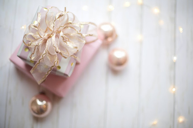 Pink present with a golden bow. There are fairy lights and baubles around the gifts
