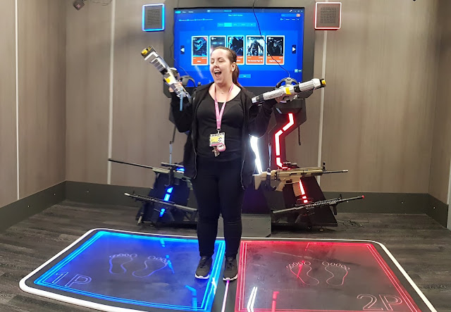 x gen VR manager Lily with both guns in hand demonstrating 2 player shooting VR game