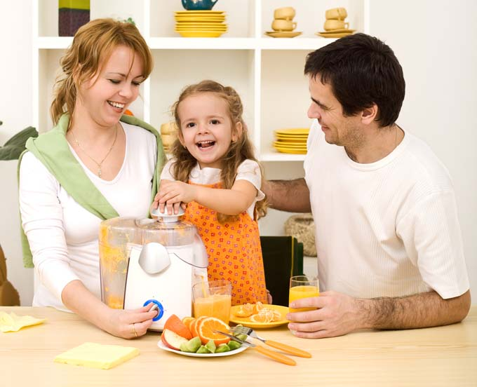 A mother, father, and you girl gather around a juicer on the kitchen table
