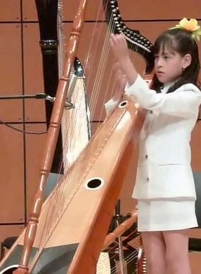 Foto de una bella niña tocando el arpa