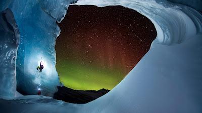 Climbing Athabasca Glacier in Jasper National Park, Alberta, Canada, as the aurora borealis glows