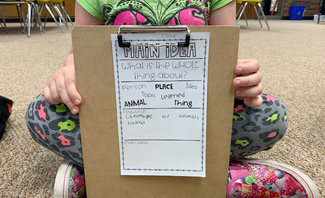Student holding a clipboard with mini main idea anchor chart