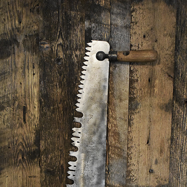 Vintage crosscut saw laying on Vancouver reclaimed wood