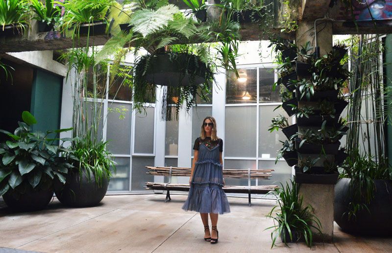 ruffle dress embroidered shirt outfit in the urban newtown lobby with hanging plants