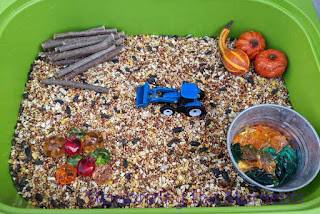 Fall tractor sensory play with apples, pumpkins and leaves