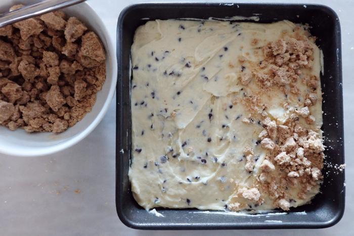 adding crumb topping to cake batter in pan