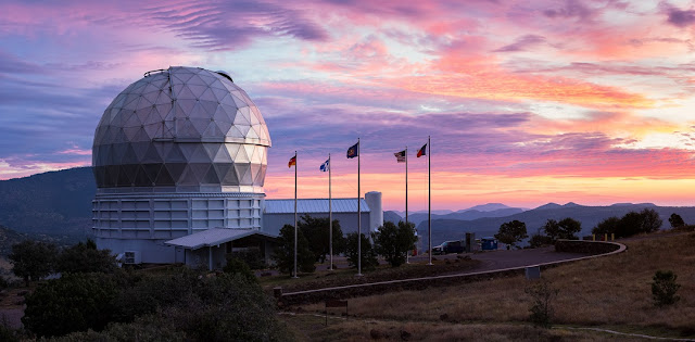 The dome of the Hobby-Eberly Telescope sits at left with a backdrop of a multi-colored West Texas sunset. Credit: Ethan Tweedie Photography
