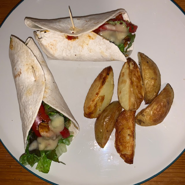 Mango chutney chicken wraps with peppers and lettuce, with potato wedges
