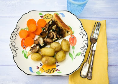 Garlic mushroom tart on a white plate with new potatoes and carrot slices