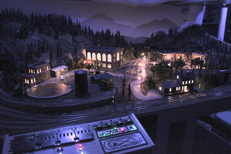 HO scale model railroad layout and control panel at night with accessory lighting effects
