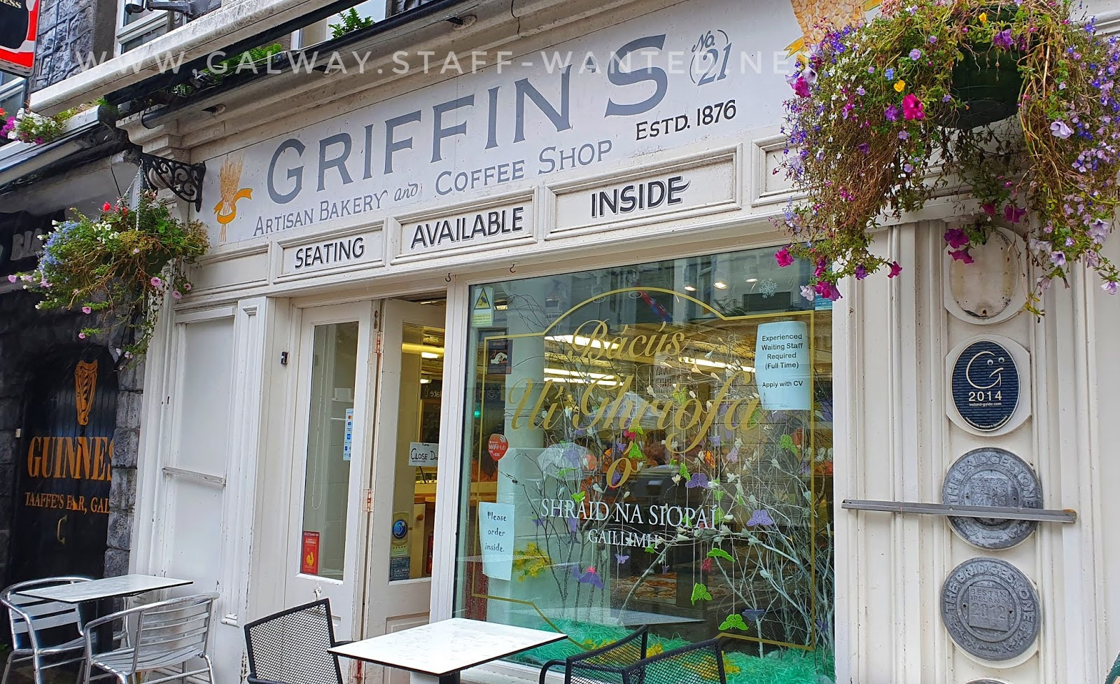 Griffins artisan bakery and coffee shop front, with outdoor tables and hanging floral decoations, and the side door of Takffes pub in the background.