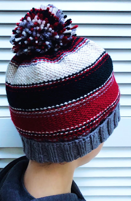 Knitted hat with pompoms in grey, red, white, and black