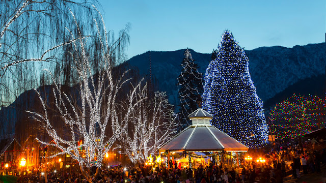 a large group of people focused on a festively lit pavilion