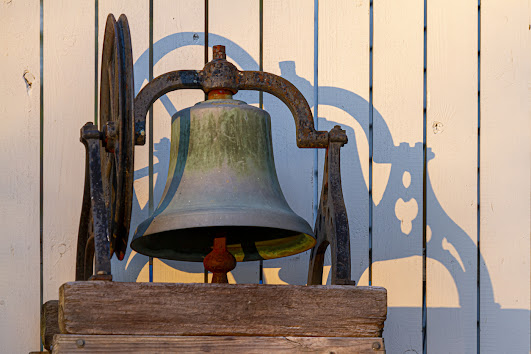tarnished brass bell on wood stand