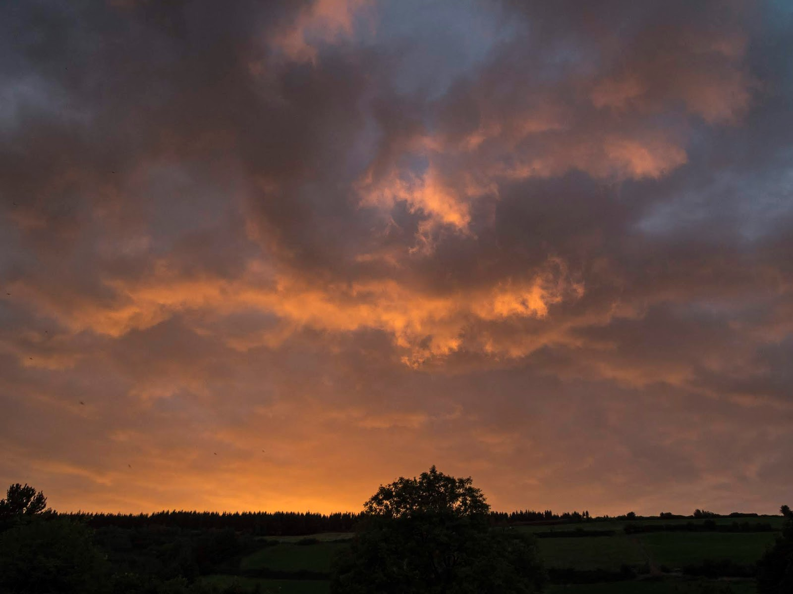 Bright orange sunset clouds over a mountain side in North Cork.