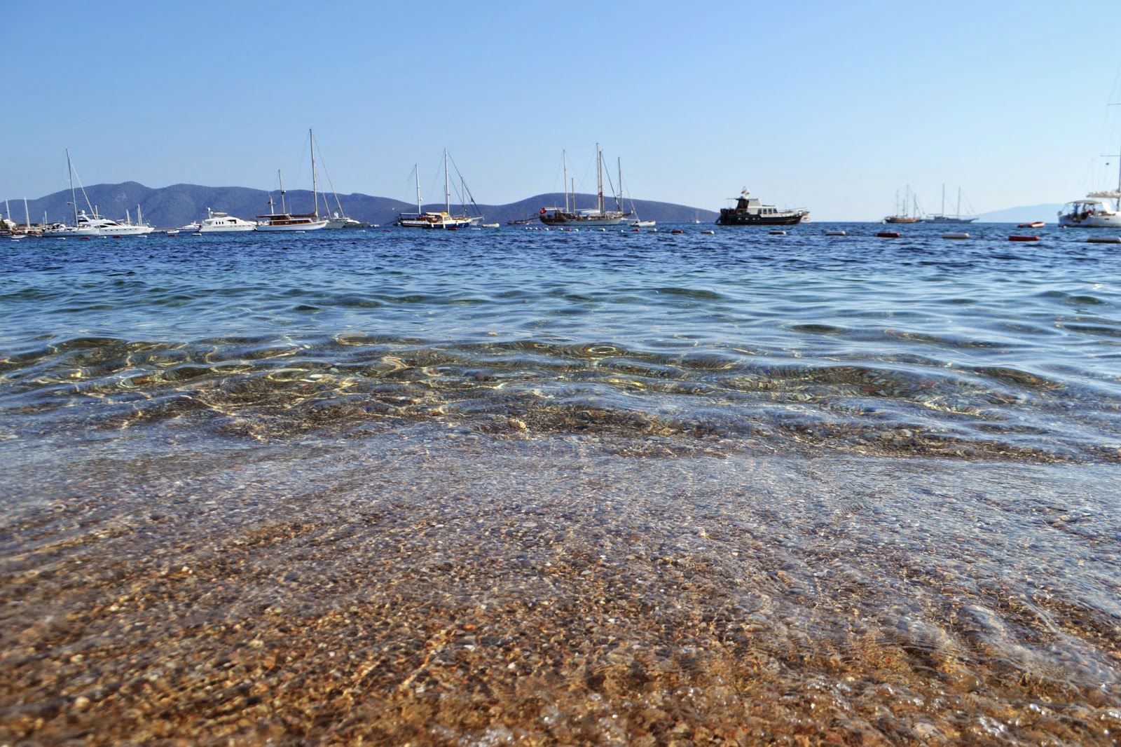 Photo taken from the shore or Bodrum beach. Looking out across the bay at the clear waters and the boats in the distance.