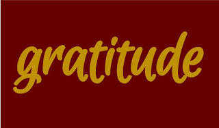 gratitude cursive script in yellow with maroon background