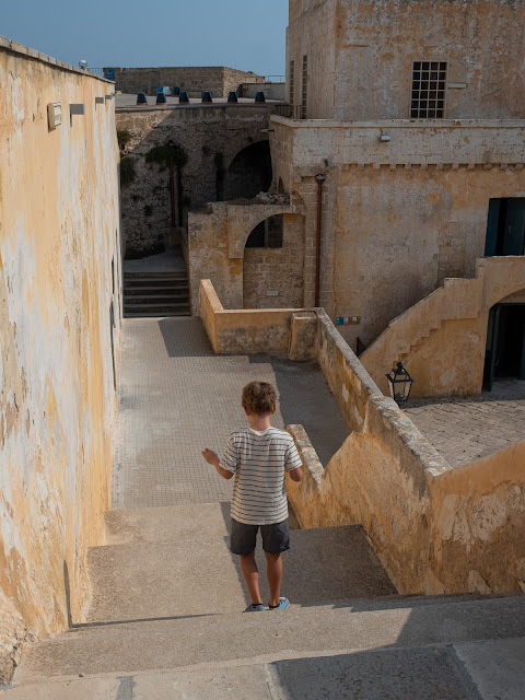Niño de espaldas bajando las escaleras dentro de las muros amarillos del castillo de Gallipoli