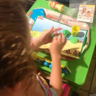 Girl working with Play-Doh stamps