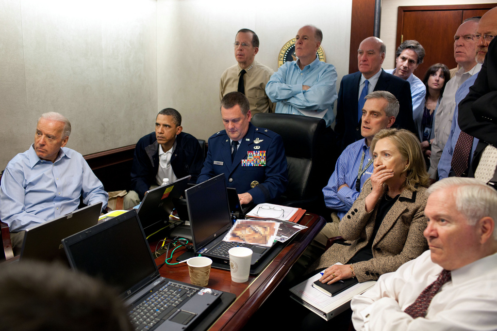 "President Barack Obama and Vice President Joe Biden, along with members of the national security team, receive an update on the mission against Osama bin Laden in the Situation Room of the White House, May 1, 2011. Seated, from left, are: Brigadier General Marshall B. ""Brad"" Webb, Assistant Commanding General, Joint Special Operations Command; Deputy National Security Advisor Denis McDonough; Secretary of State Hillary Rodham Clinton; and Secretary of Defense Robert Gates. Standing, from left, are: Admiral Mike Mullen, Chairman of the Joint Chiefs of Staff; National Security Advisor Tom Donilon; Chief of Staff Bill Daley; Tony Blinken, National Security Advisor to the Vice President; Audrey Tomason Director for Counterterrorism; John Brennan, Assistant to the President for Homeland Security and Counterterrorism; and Director of National Intelligence James Clapper. Please note: a classified document seen in this photograph has been obscured. (Official White House Photo by Pete Souza)"