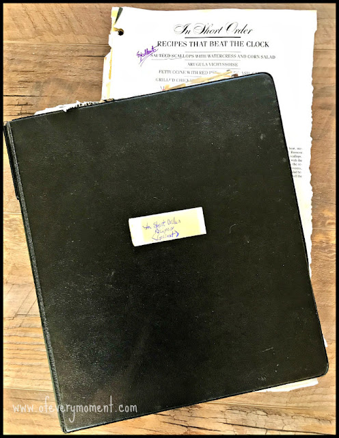 """A black three-ring binder, labeled """"In Short Order Recipes (Gourmet)"""" with some torn-out recipe pages from a magazine poking out from it."""