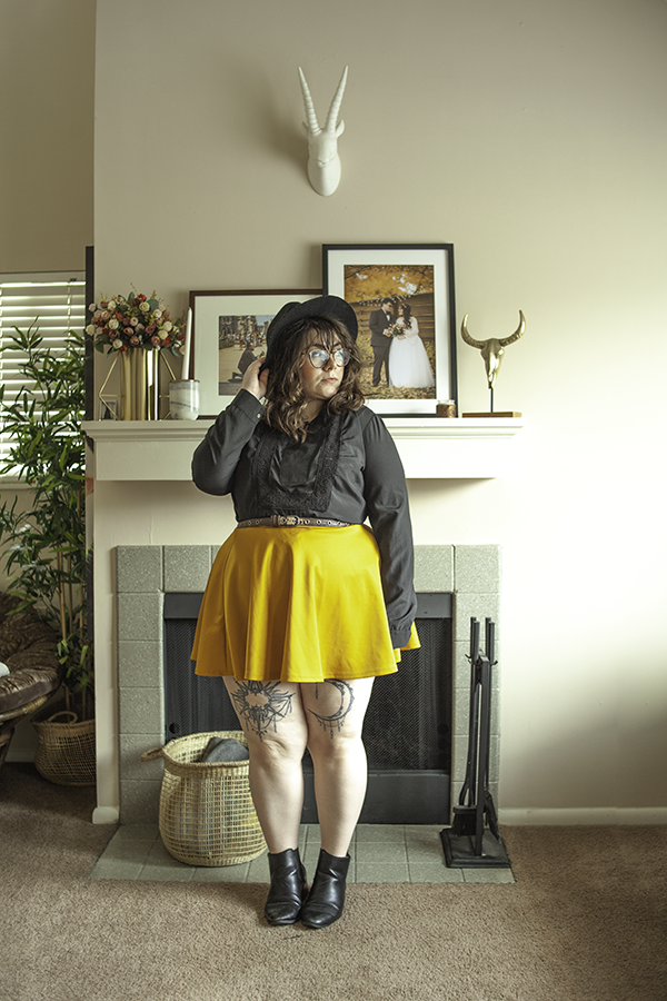 An outfit consisting of a black wide brim fedora, a black peasant blouse with a keyhole cut out in the front, a mustard yellow skater skirt and black heeled Chelsea boots.