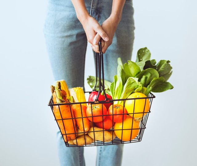 Woman holding a basket filled with food groceries