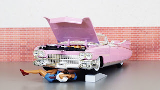 pink dolls car with doll under hood