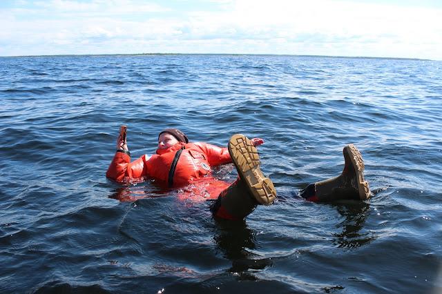 Pelastautumispukuun pukeutunut luontokartoittaja kelluu veden pinnalla ja ottaa valokuvaa