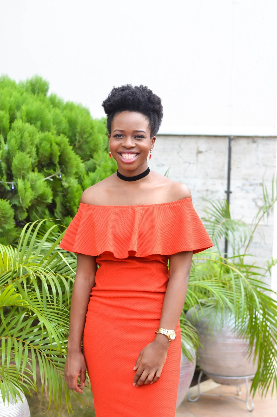 Red Off Shoulder Dress on a Smiling Woman of Colour