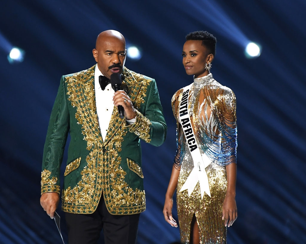 Steve Harvey and Miss South Africa Zozibini Tunzi speak onstage at the 2019 Miss Universe Pageant at Tyler Perry Studios on December 08, 2019 in Atlanta, Georgia. (Photo by Paras Griffin/Getty Images)