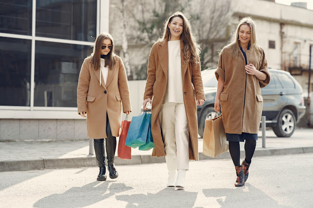 Three girls in tan jackets, laughing, and walking while carrying shopping bags.
