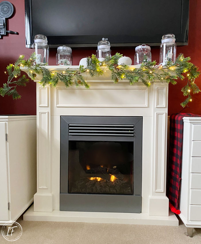 A quick, easy, and cheap Christmas mantel decorating idea for a fireplace with large Tv. Festive minimalist winterscape DIY Christmas decor.