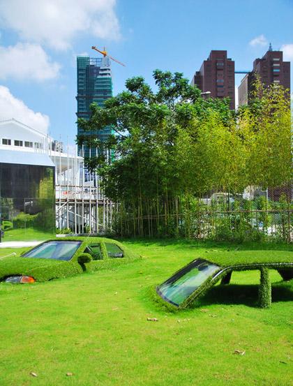Jardín con autos hundidos en el pasto.