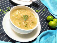 Serving lemon coriander soup in a soup bowl, lemon in background