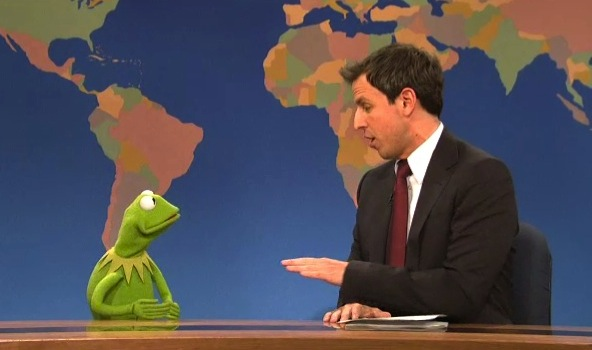 Kermit the Frog and Seth Myers in conversation at 'Weekend Update' desk.