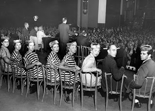 Black and white image of five women sitting in wooden chairs, they are turned around in their chairs to face the camera, each is wearing a black and white striped 'prison uniform' and there are two men and a woman, not in uniform, similarly seated. They appear to be on a stage as a seated crowd is visible beyond.
